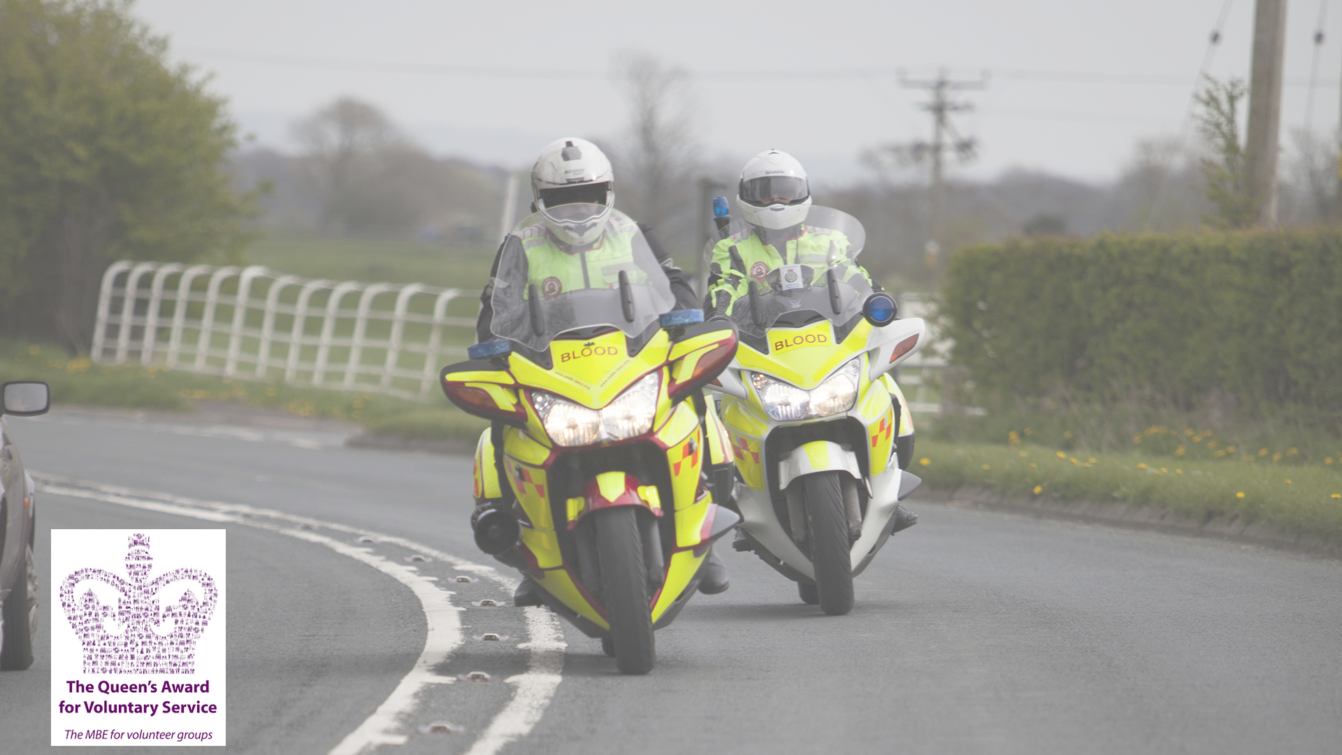 Two Blood Bikers riding down a road