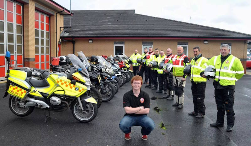 Group of blood bikers with liveried and non-liveried bikes at fire station.